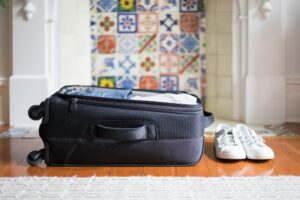 Small overnight weekender black suitcase with wheels packed with clothes,